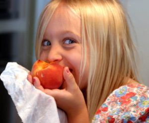 Ребёнок ест фрукт с косточкой