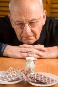 Старик ест таблетки