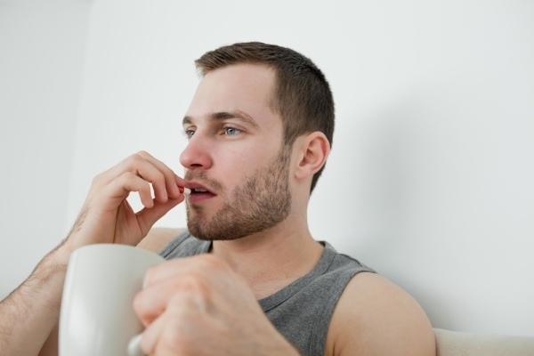 Человек запивает водой таблетку