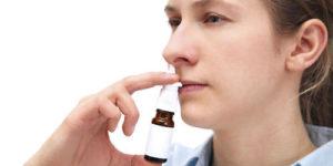 Человек с насморком капает в нос