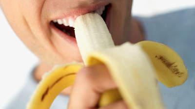 Человек ест банан