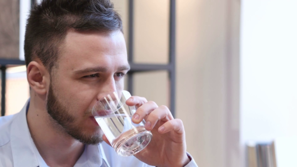 Человек пьёт из стакана