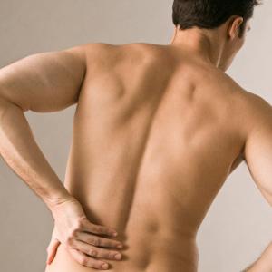 Человек держится за спину и согнулся от боли
