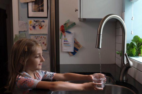 Ребёнок наливает воду из-под крана