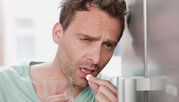 Человек пьёт таблетку