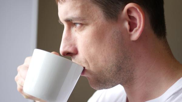 Человек пьёт воду из кружки