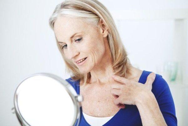 Женщина осматривает шею в зеркале