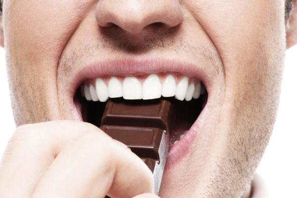 Человек ест шоколад